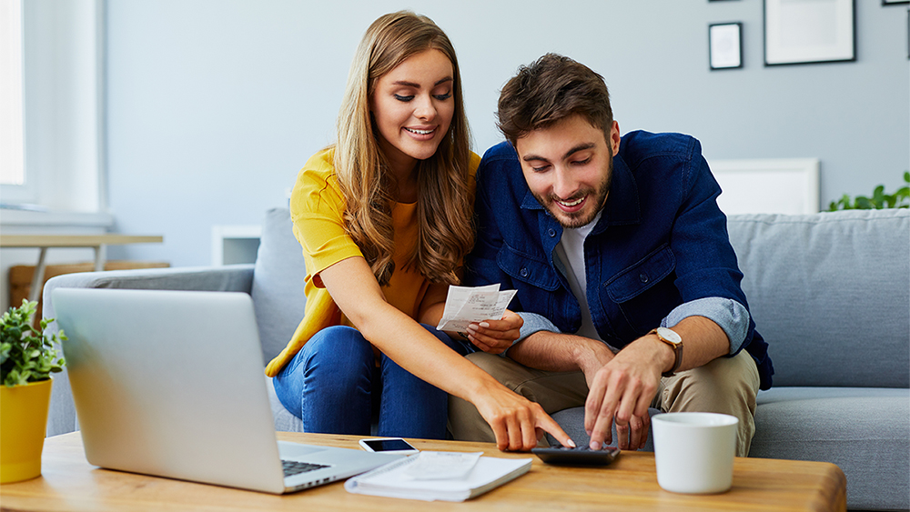 couple on sofa with laptop, bills and calculator