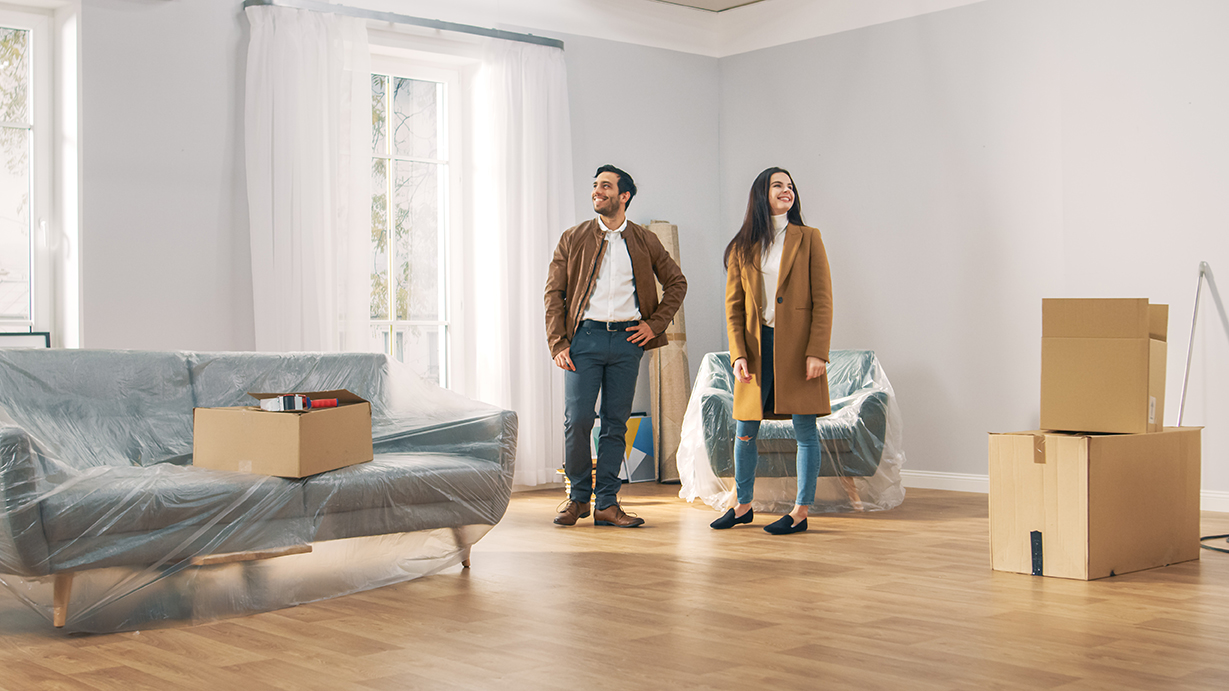 couple in room with packing boxes and sofa