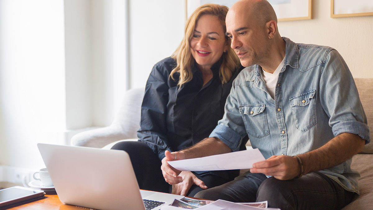 couple with laptop looking at reno plans