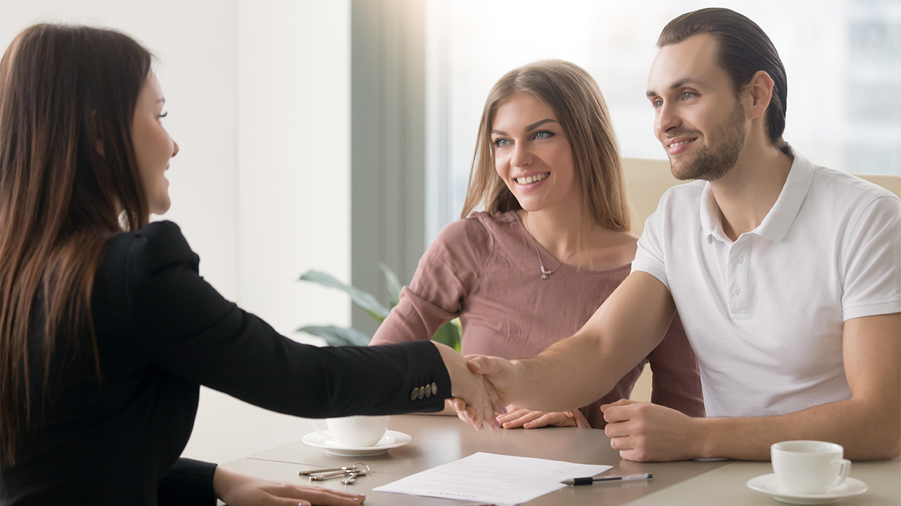 couple with agent shaking hands across a table